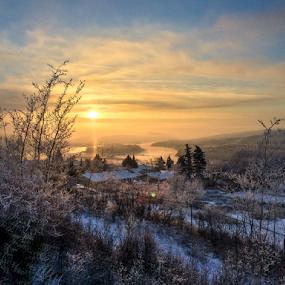Peace River Winter Evening by Charles Adam - Landscapes Sunsets & Sunrises ( clouds, pines, hills, houses, frost, frozen, dusk, sun, island, fence, hillside, winter, cold, fog, sunset, snow, bush, evening, river )