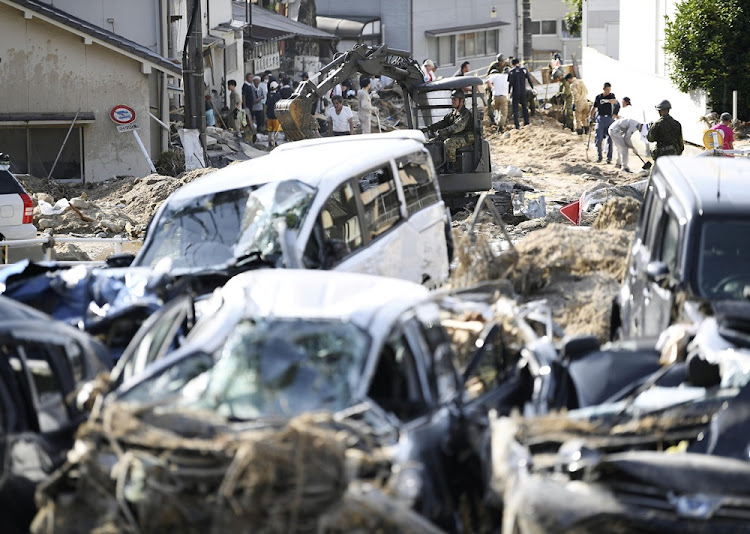 People clear debris caused by torrential rain at Aki ward in Hiroshima, Hiroshima Prefecture, Japan, in this photo taken by Kyodo on July 10 2018.