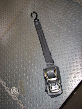 Photo: This strap works like a seatbelt. It pulls out of the base, over the tire and ties to a hook in the deck. The single bolt in the base can attach to the truck bed or be attached to a chock - the chock would then be attached to the truck bed.
