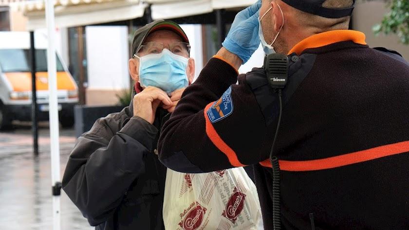 Protección civil enseña cómo colocarse la mascarilla a un anciano.