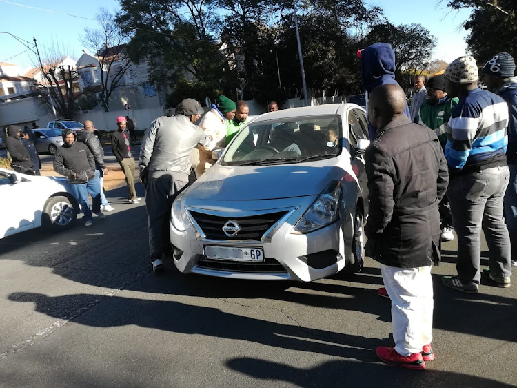 Uber and Taxify operators stop some of their fellow drivers near Zoo Lake in Johannesburg as they embark on a strike on July 3 2018.