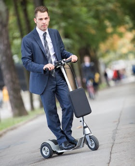 Man in suit riding electric scooter