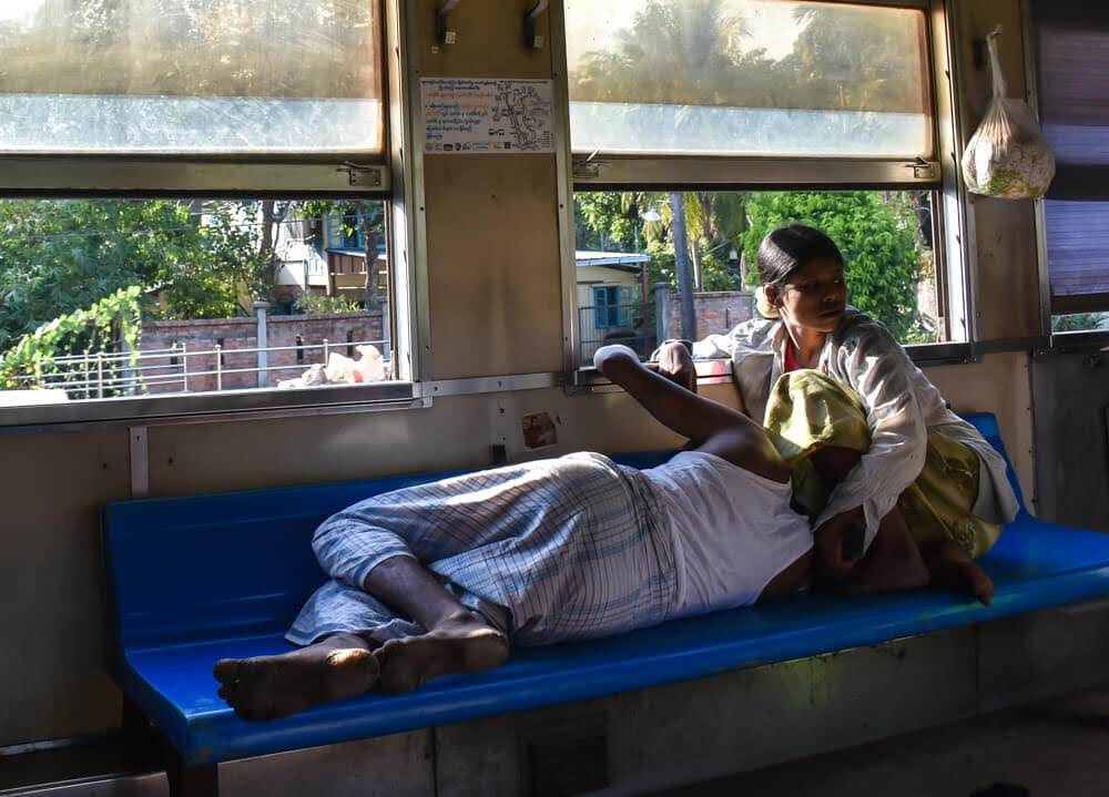 man and woman sleeping in yangon circular railway train burma