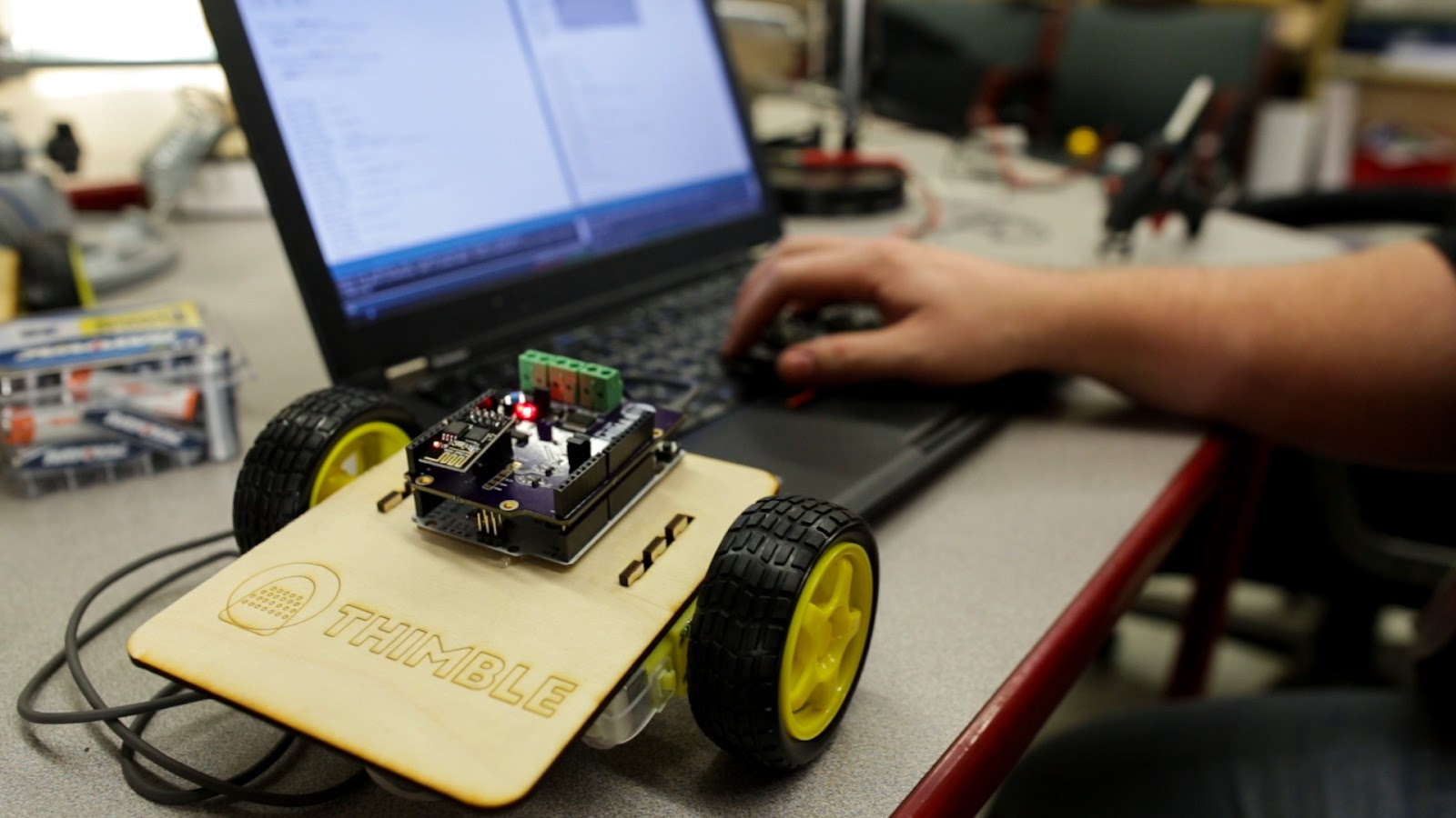 This is an image of a completed Thimble Wifi Robot Kit sitting on a table next to a keyboard and computer. There is a hand typing on the keyboard.