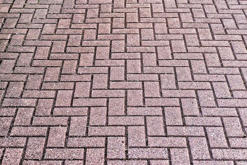 A brick outdoor flooring that is made of red brick and laid in a zig zag pattern.