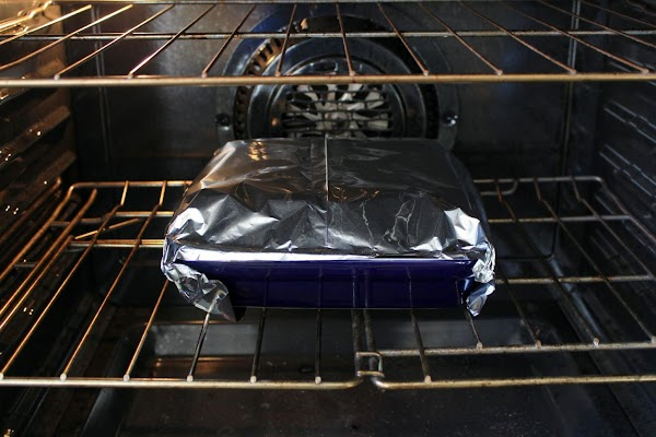Sandwiches covered in foil and baking in the oven.
