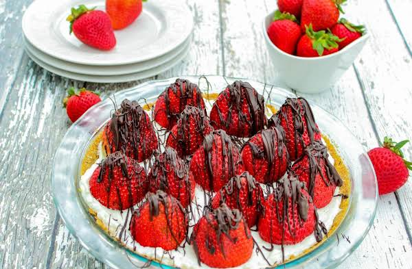 Strawberry Pie With Chocolate Drizzled On Top.