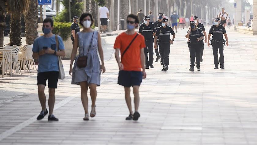 Gente con mascarillas y control policial en Paseo Marítimo de Almería, en el día de ayer.