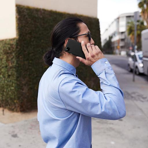 青色のシャツを着た人物が、Google Pixel を持っています。