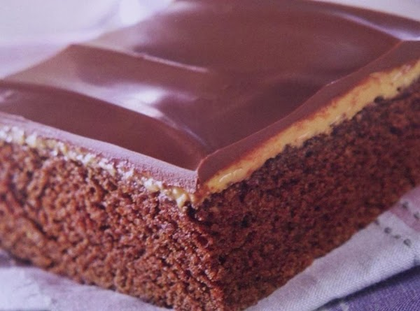 Carefully spread chocolate topping over top of cake, covering peanut butter. Allow topping to...