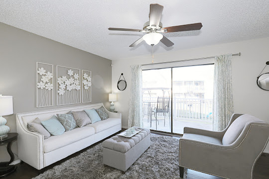 A3 floorplan spacious living area with a ceiling fan, sliding glass door leading out to a patio and wood-style flooring