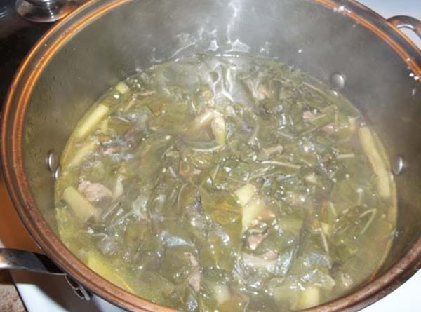 Place the cut up luau leaves in the pot along with the stems and...