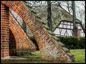 Photo: Die ursprünglich backsteingotische Dorfkirche wurde im 14. Jahrhundert errichtet und im 17. Jahrhundert einer größeren Umgestaltung unterzogen. Die dahinterliegende Pfarrscheune wurde im Jahre 1702 gebaut und ist das älteste weltliche Gebäude in Dorf Mecklenburg bei Wismar.