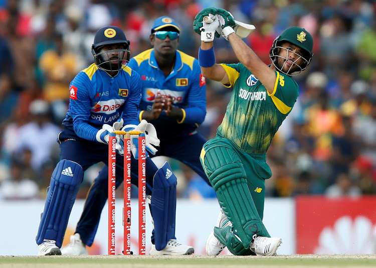 South Africa's JP Duminy (R) hits a boundary next to Sri Lanka's wicketkeeper Niroshan Dickwella (L) and captain Angelo Mathews (C) during the first ODI match in Dambulla on July 29, 2018.