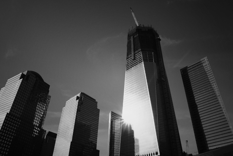 Photo: The Freedom Tower (One World Trade Center) rising above the 9/11 Memorial.  The Memorial is a national tribute of remembrance and honor to the 2,983 people killed in the terror attacks of September 11, 2001 and February 26, 1993. It opened on September 11th, 2011. I visited on September 19th, 2011.  The two fountains at the memorial site are surrounded by granite borders that contain the names of all those who were killed in both terror attacks at the site.  Together they make up the nation's largest manmade waterfalls, and are at the heart of the design of the memorial, called Reflecting Absence.  Image by Vivienne Gucwa. You can view more photography by Vivienne Gucwa at her website:   http://nythroughthelens.com/