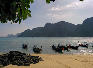 Photo: The classic view of Ko Phi Phi: white-sand beach, a blue-green sea, long-tail boats, and distant cliffs.