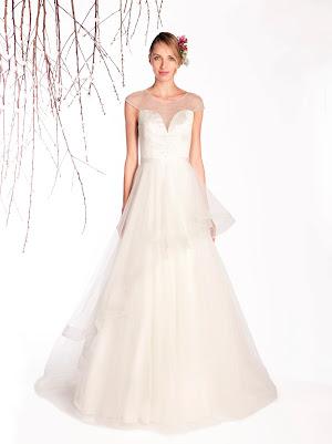 Robe de mariée Envie, esprit princesse, en tulle et satin avec des petits strass sur le bustier et des volants asymétriques sur la jupe, les petites manches courtes qui affinent les bras
