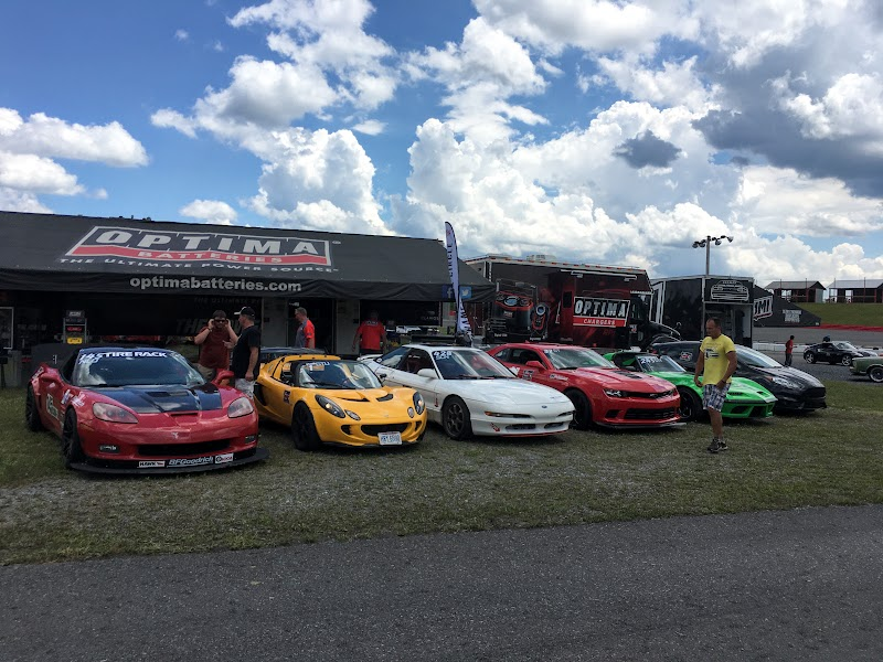 A Corvette, Lotus, Probe, Camaro, Corvette, and a Fiesta in front of Optima's trailer