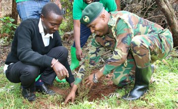 A man helps KFS Chief Conservator of Forests Julius Kamau to plant a tree