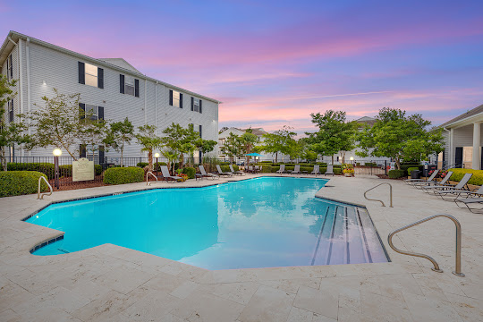 Cypress Pointe apartment swimming pool with lounge chairs at dusk
