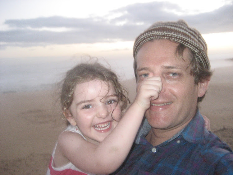 A portrait of the author as a young man posing with his daughter, Phoebe, during a seaside holiday.
