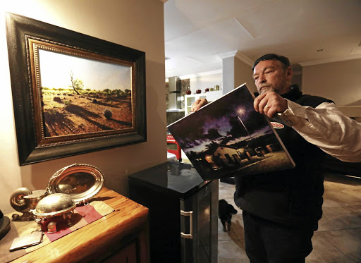 Steve Botha examines the back of one of Meyer's last paintings, showing his house in Upington at night.