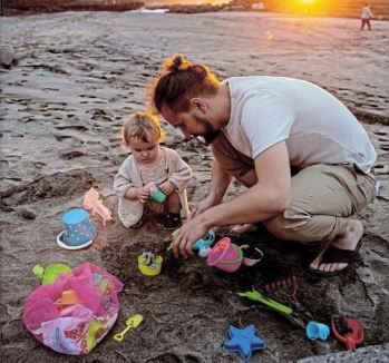 A toddler watches closely while playing on the beach with her dad. There must always be roommfor people to let loose and have fun, says the writer.