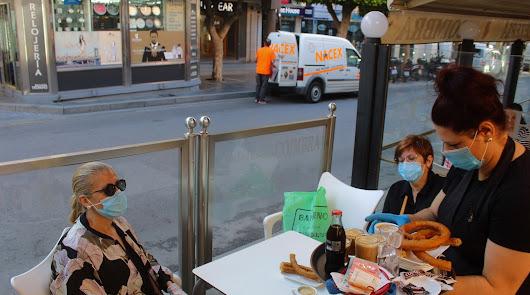 Una camarera atiende a dos clientas en una terraza del Paseo de Almería.