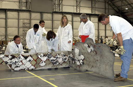 Members of the Columbia Reconstruction Project Team look at a large piece of Columbia debris.