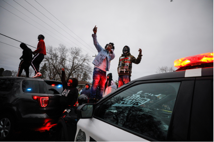 Demonstrators stand on a police vehicle during a protest after police allegedly shot and killed a man, who local media report is identified by the victim's mother as Daunte Wright, in Brooklyn Center, Minnesota, US, on April 11 2021.