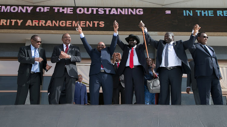 South Sudan's president Salva Kiir (with hat) holds hands with South Sudanese rebel leader Riek Machar as Sudan's president Omar al-Bashir and Kenya's president Uhuru Kenyatta witness before the signing a ceasefire and power sharing agreement in Khartoum, Sudan earlier this month.