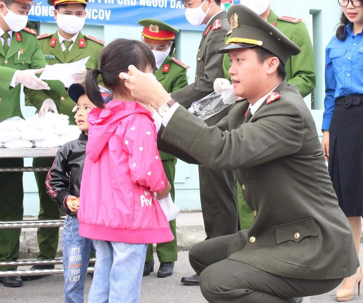 Đại úy Nguyễn Đình Khánh, Bí thư Đoàn Thanh niên Công an tỉnh đeo khẩu trang cho một em nhỏ