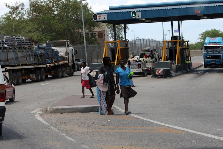 Zimbabweans go about their business near the Beitbridge border post in Musina yesterday.