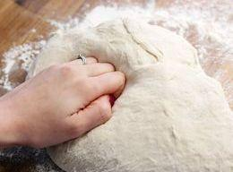 Punch the dough down and pour out on a floured surface. Knead the dough,...