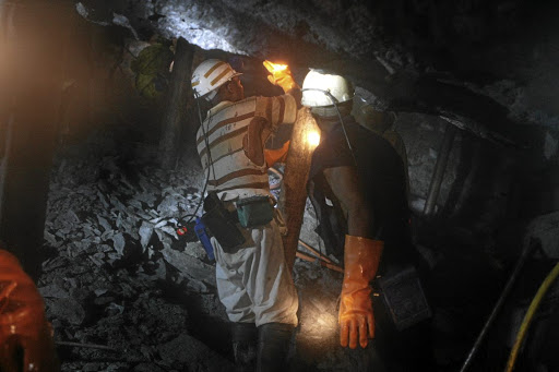 Cramped conditions: Mine workers working 1km underground at the Harmony Cooke shaft 3 mine. Picture: MARIANNE SCHWANKHART