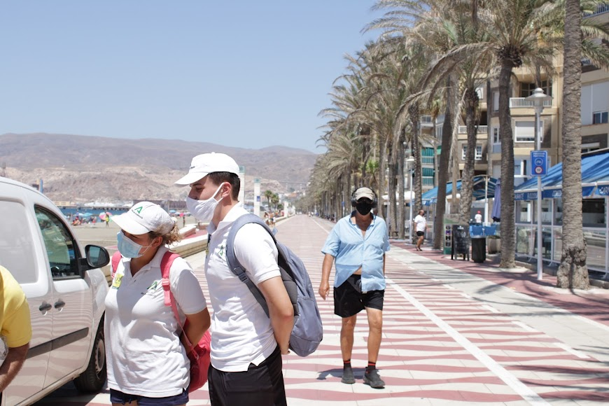 Auxiliares de playa y ciudadanos por el Paseo Marítimo y con mascarillas.