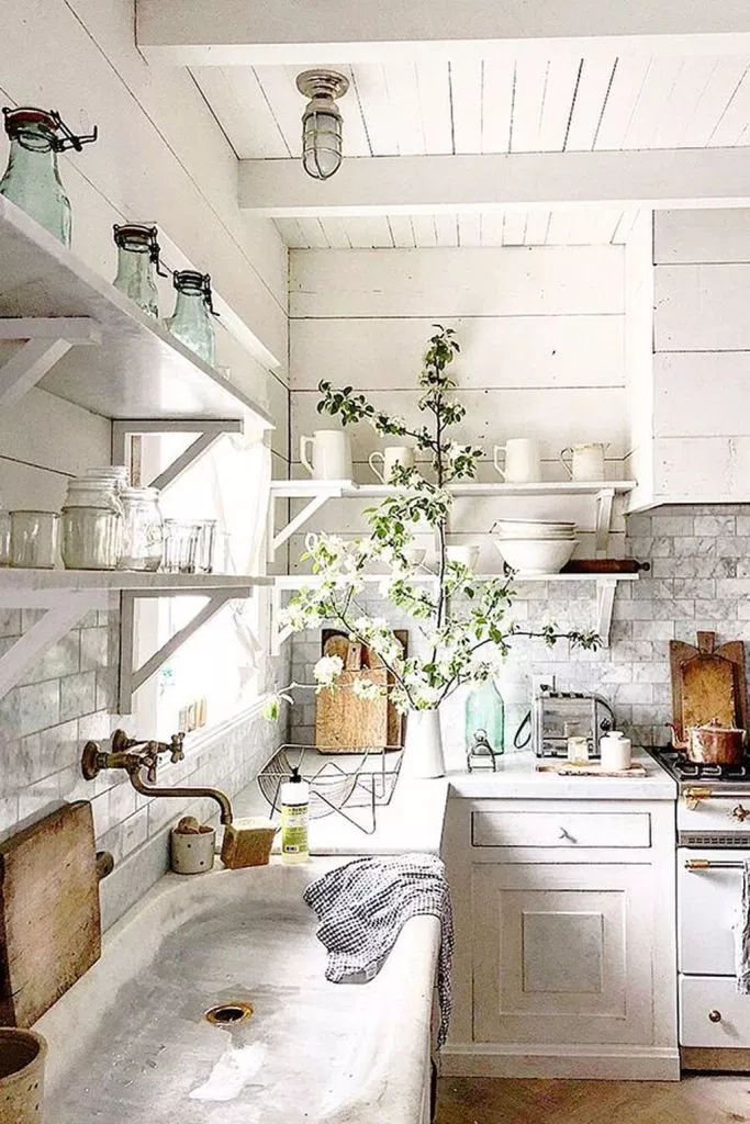 classic farmhouse kitchen with shiplap walls, white vintage cabinets, small farmhouse cabinets, cement countertops, large basin sink and vintage farmhouse decor