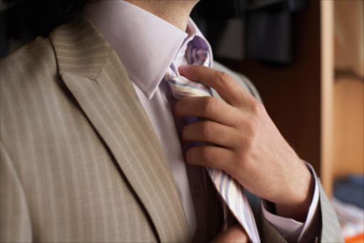 Man adjusting tie. File photo.