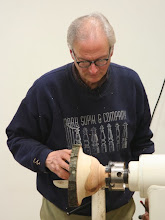 Photo: The outside is shaped, and Mark reverses the bowl into a chuck.  Mark has no problem bottoming the tenon out in the chuck, although many instructors will say not to.