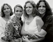4 vrouwen die naast elkaar staan en elkaar vasthouden