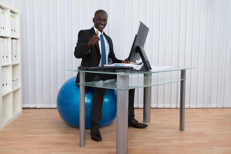 Businessman working and sitting on a pilates ball.