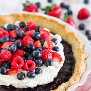 Blueberry Pie with Whipped Cream and Mixed Berries.