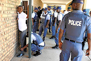 FILE PICTURE: SAPS members search a boy at Ngqayisivele High School in Tembisa, Ekurhuleni.