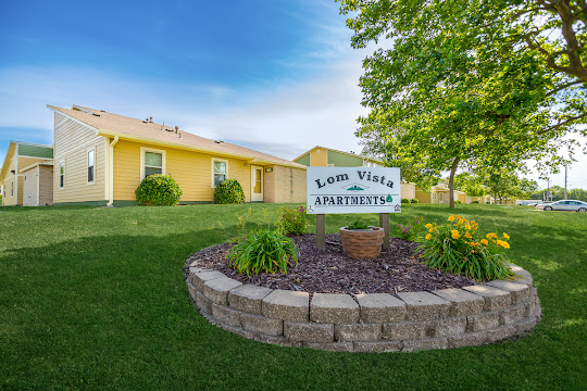 Lom Vista Apartment outdoor sign with stone wall and landscaping