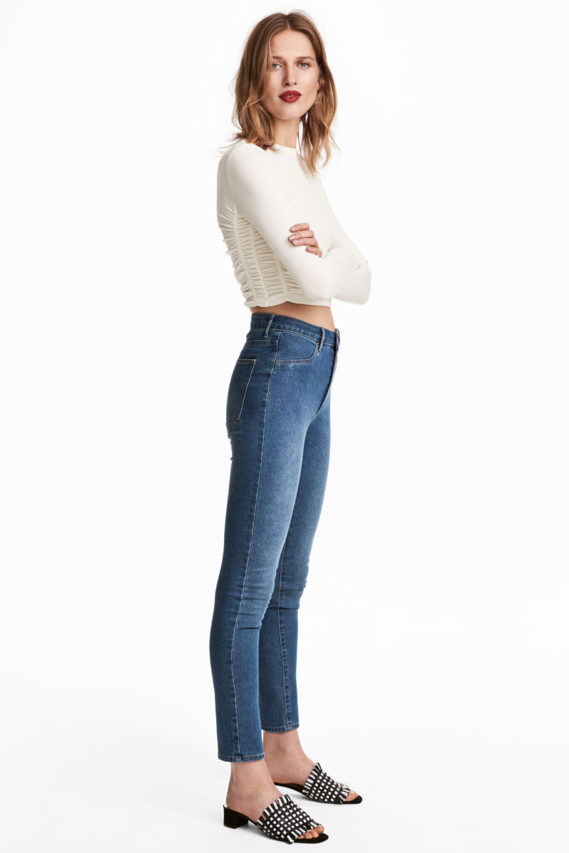 Woman wearing white long-sleeve crop top with high-ankle denim skinny jeans.