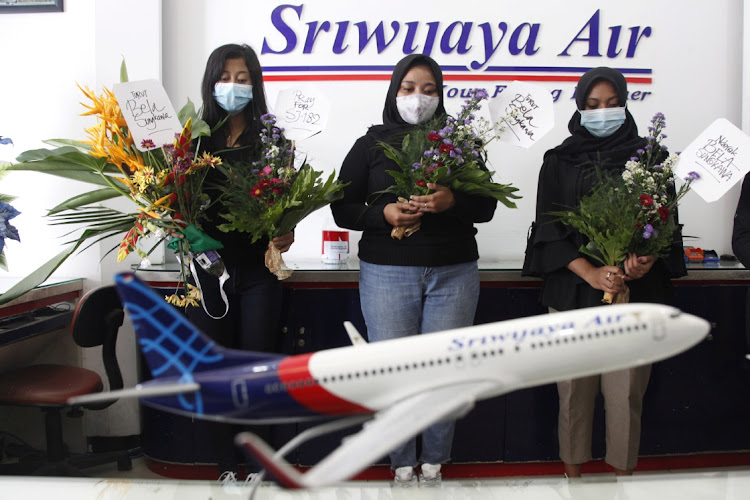 Women hold a vigil for passengers of Sriwijaya Air's flight SJ182, which crashed into the sea off the Jakarta coast, in Solo, Indonesia, January 10 2021. Picture: ANTARA FOTO/MAULANA SURYA/REUTERS
