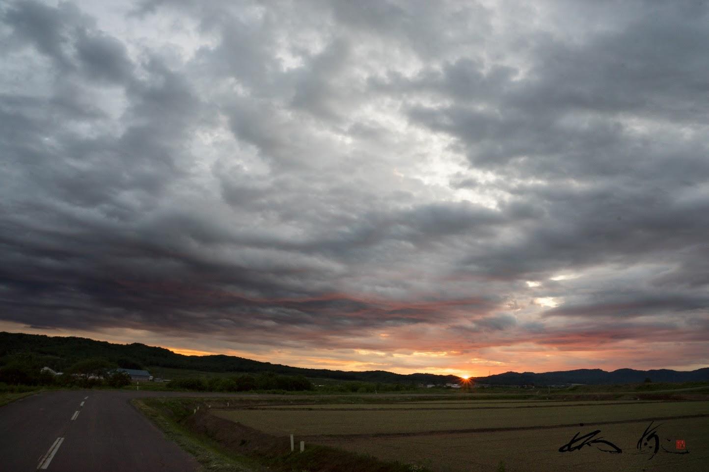 グレーな雲に滲む夕陽