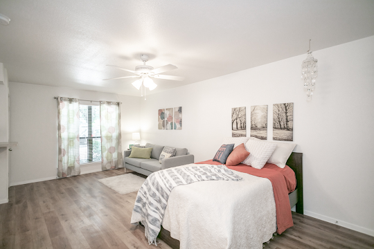 Studio bedroom with wood inspired floors and white walls