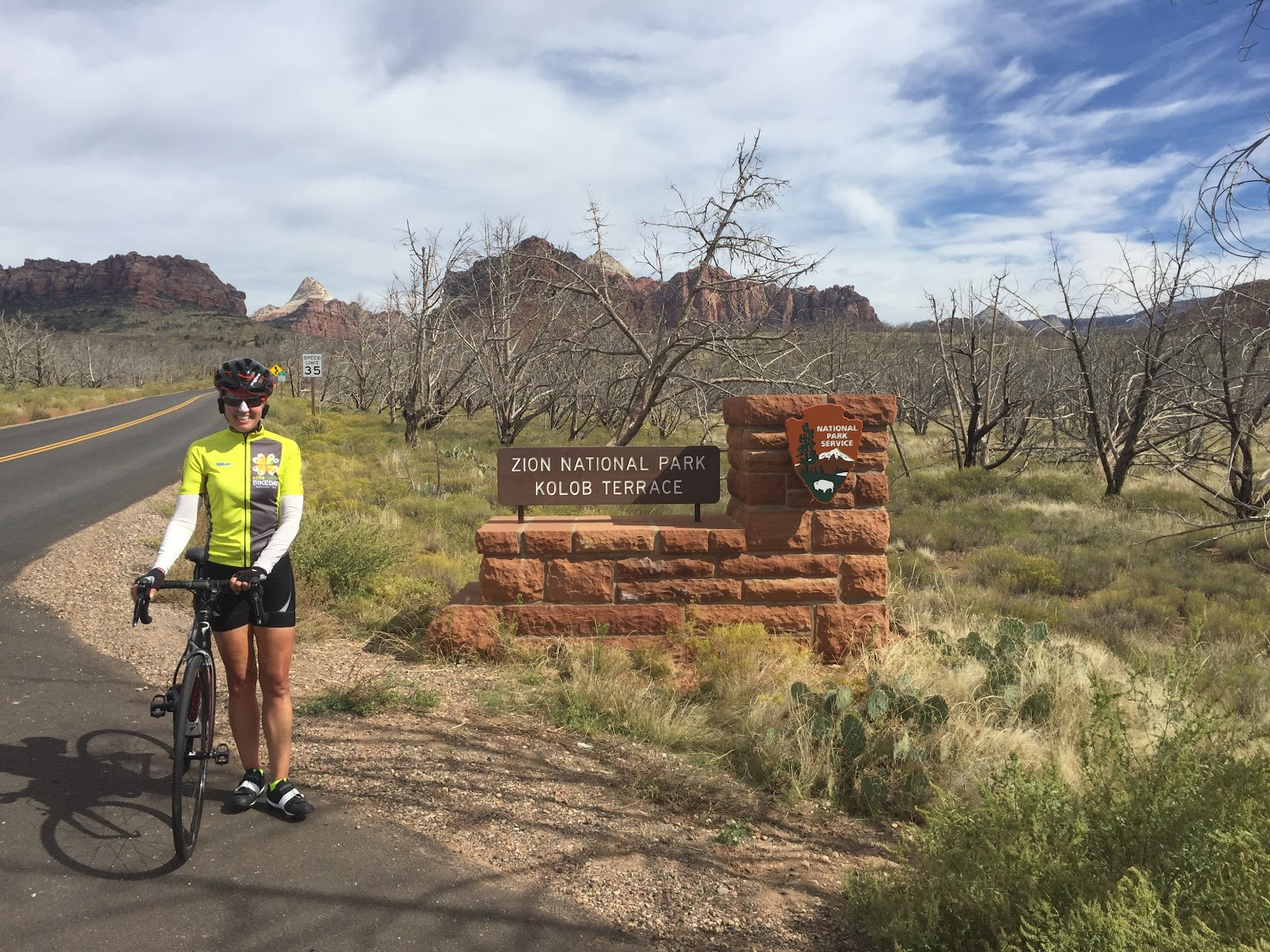 Climbing Kolob Terrace by bike - cyclist at Zion National Park Sign with bike
