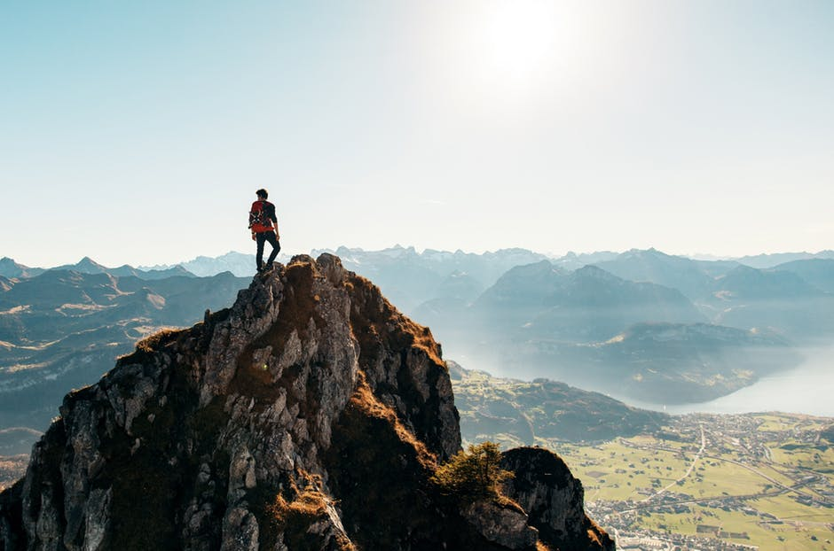 Man Standing on Brown Rocking Mountain Under Blue Sky and Yellow Sunlight